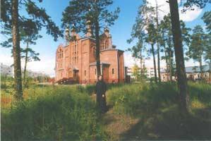 Священник Михаил Зайцев на фоне храма Казанской иконы Божьей матери. г. Нерюнгри